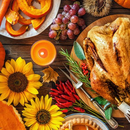 Thanksgiving dinner. Roasted turkey with pumpkins and sunflowers on wooden table